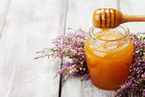 Pouring honey in jar and flowers heather on wooden rustic table. Copy space for text.