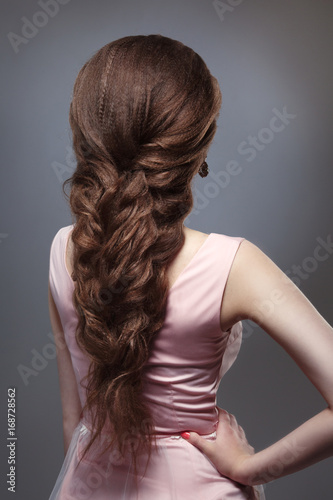 Elegant wedding braided voluminous hair on long dark hair. © ksi