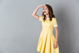 Pretty young girl in dress standing and looking far away - 168739792