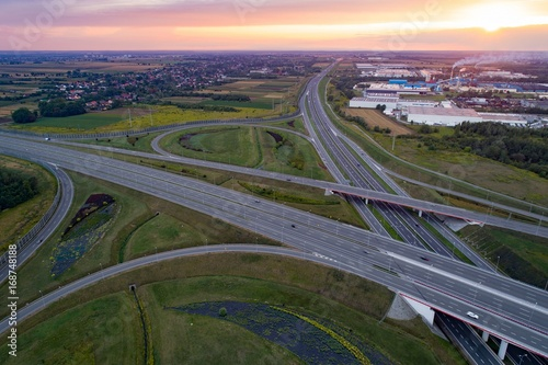 Foto op Plexiglas Nacht snelweg Sunset over the highway junction and industrial zone
