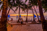 Sunset in tropical island of boracay with white beach and coconut palms in philippines
