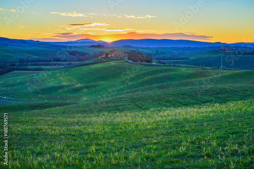 Fotobehang Nachtblauw Sunset over the green hills in the Tuscan countryside in the province of Siena Italy.