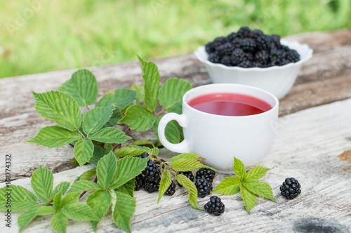 Fotobehang Thee Cup of tea and blackberry plate