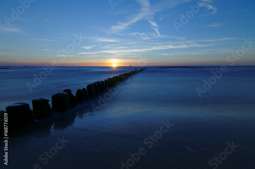 Poland, Baltic. Sunset over the sea. Breakwater on the smooth surface of the sea.