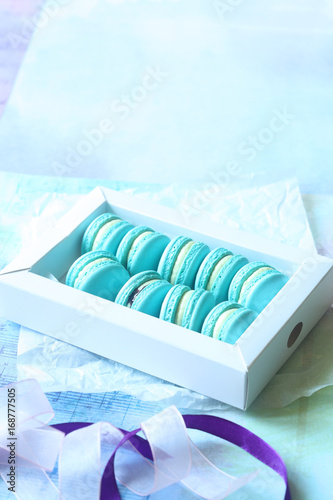 Fotobehang Macarons Blue Macarons with Cream Cheese and Blueberry Filling in a white box, on light blue background.