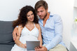 happy pregnant woman and her husband with tablet pc at home