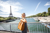 Elegant french business woman walking the bridge with Eiffel tower on the background during the sunny weather in Paris