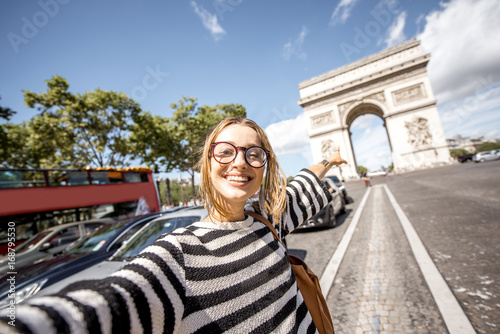 Poster Young woman tourist making selfie portrait with famous Triumphal Arch on the background in Paris