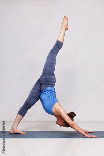 Woman doing Hatha yoga Eka pada adhomukha svanasana