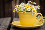 Yellow cup filled with chamomile flowers on wooden plank table.