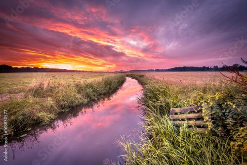 Fotobehang Purper Warm indian summer sunrise over lowland river in vintage colors