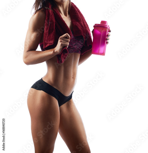 Poster Cropped studio shot of a sportswoman with sexy toned body holding sports bottle posing with a towel on her shoulder relaxing after exercising
