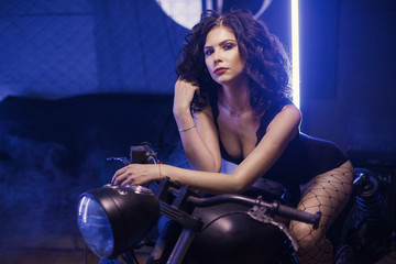 Curly biker girl in black lingerie sitting on old fashioned motorcycle in interior on blue lights background