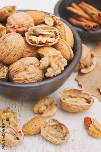 walnuts and almond on black bowl on wooden background Poster
