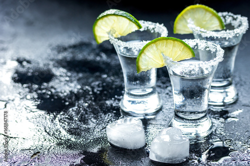 Tequila shot with lime slices and salt on dark background