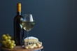 Bottle and glass with white wine near cheese composition on a wooden board