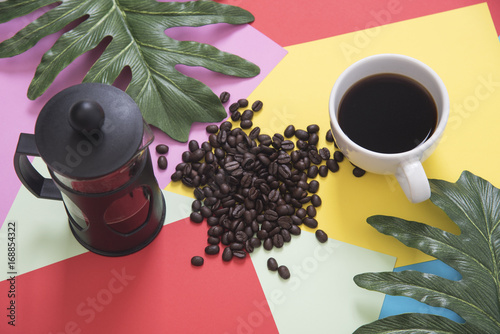 Top view flat lay of coffee cup with french press, coffee beans, leaves on color background.