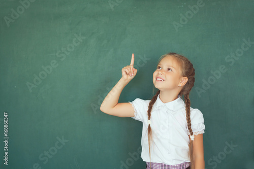 Fototapeta Smiling young little child girl in school on blackboard background. Education and school concept