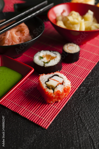 Aluminium Sushi bar Sushi rolls, ginger and wasabi on red mat and black table