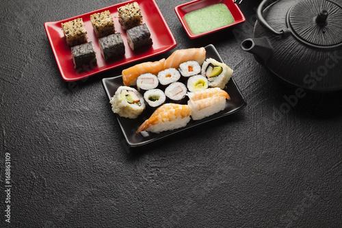 Fotobehang Sushi bar Sushi set and black teapot on black table