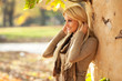 Beautiful blond hair woman standing and posing at the park on beautiful autumn day.
