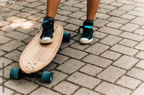 Fotobehang Skateboard Girl's leg in sneakers standing on a skateboard.
