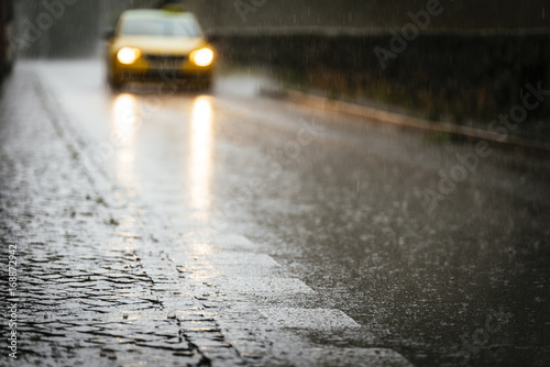 Taxi circulating on wet asphalt while its raining. Poster