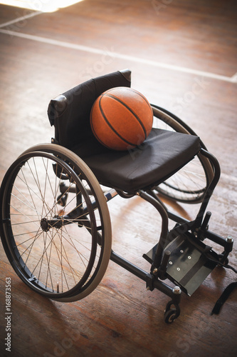 Active wheelchair with basketball on wood background - 168873563