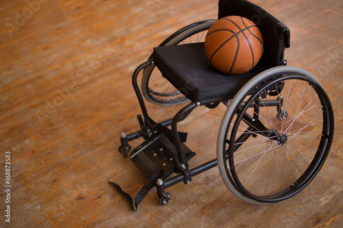 Active wheelchair with basketball on wood background - 168873583