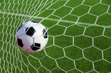 Soccer football in Goal net with green grass field. - 168882780