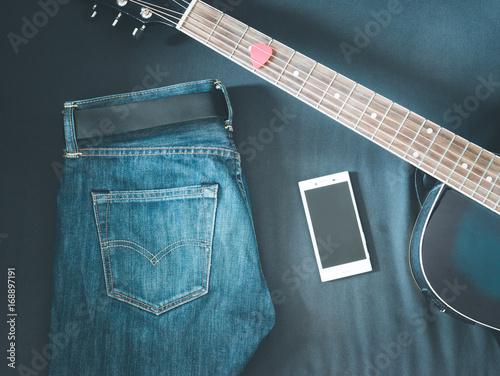 Jeans, Smartphone und Gitarrenhals