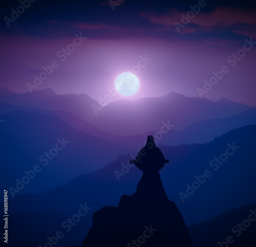Silhouette of human in a moonlight meditating