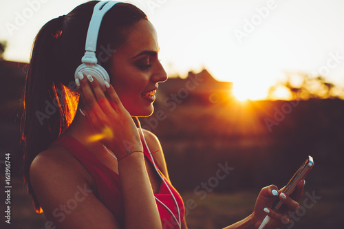 Fotobehang Muziek Beautiful young sports woman enjoy the music during the sunset
