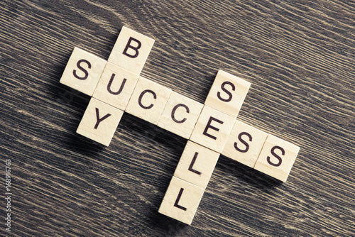 Buy sell success concepts collected in crossword on wooden table