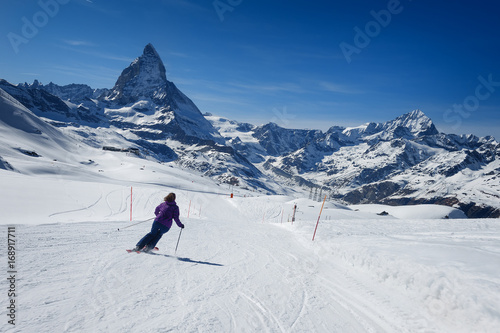 Female skier skiing on the slopes of Matterhorn mountain Poster