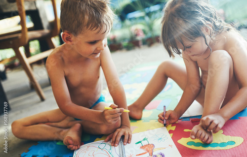 Little boy and girl drawing with crayons