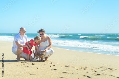 Family with girl in red dress and dog on the beach