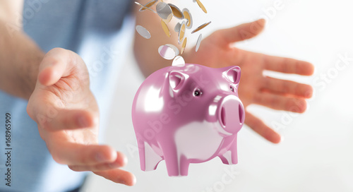 Businessman holding piggy bank with flying coins going inside 3D rendering
