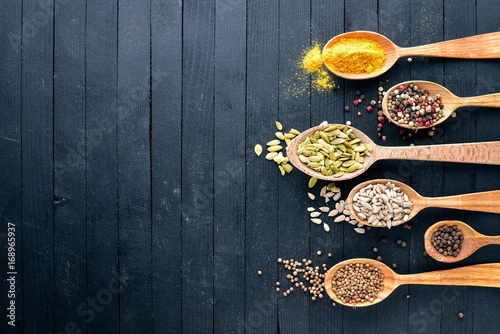 Various spices spoons on stone table. On a wooden board. Top view. Free space for your text.