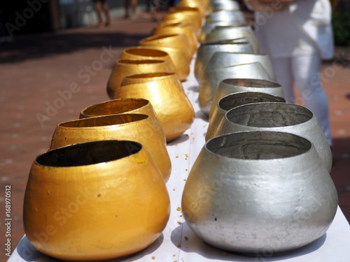 put coins in alms bowl