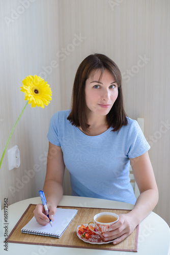 Beautiful girl in a blue dress drinking tea and writing in notepad