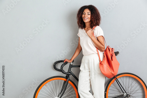 Happy african woman posing with bicycle and backpack