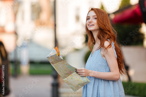 Attractive redhead girl holding a guide map