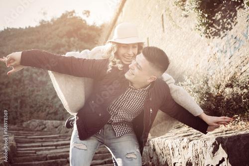 Happy couple outdoor. Boyfriend carrying his girlfriend on piggyback.
