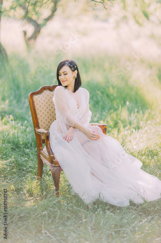 Cute woman in the long white dress and with the hair accessories looking at the right sight and sitting on the moder chair in the green spring field.