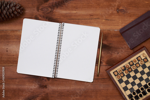 Brown wooden table with notebook Poster