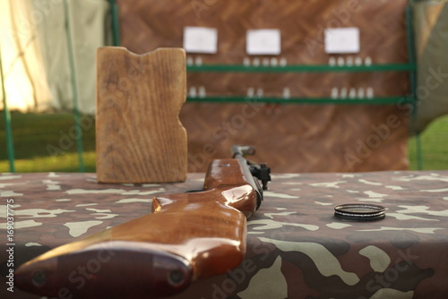 Brown pneumatic rifle on the table, focus Poster