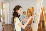 student girl with easel painting at art school - 169042921