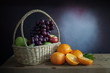 Grapes, apples and oranges  in a in wicker basket on a wooden table, still life style.