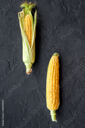 Plakát Ripe corn on cobs on black stone background top view